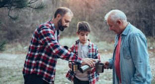 Photo of three generations males in nature drinking warm tea.