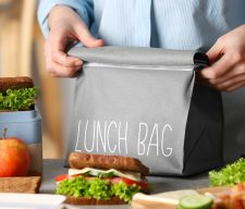 Mother packing meal for school lunch on table